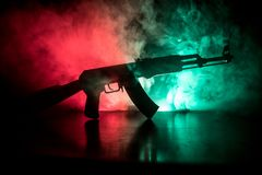 Silhouette of assault riffle on toned foggy background. War concept. Russian military weapon on table. Selective focus. Silhouette of assault rifle on toned Stock Images