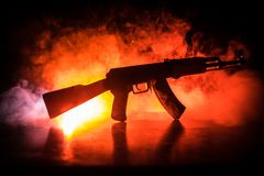 Silhouette of assault riffle on toned foggy background. War concept. Russian military weapon on table. Selective focus. Silhouette of assault rifle on toned Stock Photography