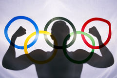 Silhouette of Athlete Behind Olympic Flag. RIO DE JANEIRO, BRAZIL - FEBRUARY 3, 2015: Silhouette of athlete flexing muscles behind the rings of Olympic flag Royalty Free Stock Photography