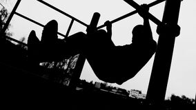 Silhouette of an athlete on a horizontal bar. Side view