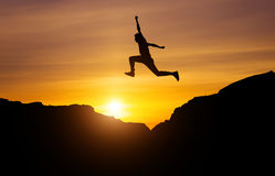Silhouette of athlete, jumping over rocks in mountain area Royalty Free Stock Image