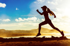 Silhouette athlete runner running in sunset. Silhouette of active healthy lifestyle athlete runner running in morning sunrise. Woman trail running on sunset Royalty Free Stock Photo