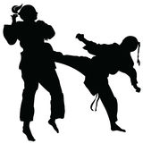 Silhouette of athletes involved in martial arts sparring.  Stock Images