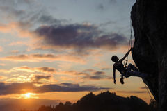 Silhouette of athletic woman climbing steep rock wall stock photo