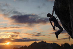 Silhouette of athletic woman climbing steep rock wall stock images