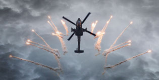 Silhouette of an attack helicopter firing flares Stock Photos