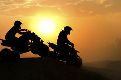 Silhouette ATV or Quad bikes Jump. In the sunset Stock Photo