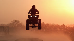 Silhouette ATV or Quad bikes Jump in the sunset. Royalty Free Stock Photo