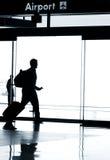Silhouette av affärsmannen som går i flygplats royaltyfria foton