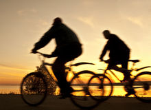 Silhouette av cyklister på soluppgången Royaltyfri Bild