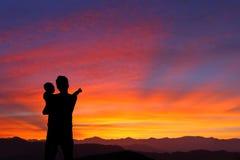 Silhouette av den hållande ögonen på soluppgången för fader och för barn Royaltyfri Foto