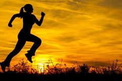 Silhouette av den running flickan på soluppgången Royaltyfria Foton