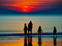 Silhouette av en familj i solnedgången Arkivbild