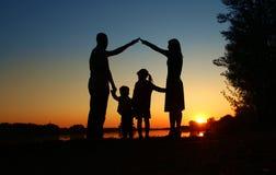 Silhouette av en lycklig familj arkivbild