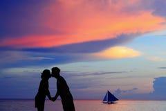 Silhouette av en ung brud och brudgum i strand Arkivbild