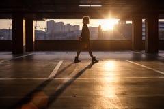 Silhouette av flickan Flicka som sopar parkeringsplatsen för bilar Royaltyfri Bild