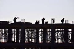 Silhouette av folk arbete och byggnadskonstruktion Royaltyfria Foton