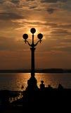 Silhouette av lampan med sunen och moln Arkivfoton