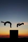 Silhouette av tonåringar som gör som är freerunning i solnedgång Arkivfoton