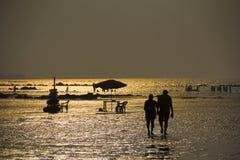 Silhouette avec des couples marchant sur la plage, l'eau de mer brillante et d'autres personnes, plage de Kihim, Alibag image stock