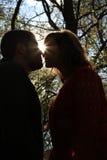 Silhouette avec la fusée du soleil des couples de baiser se tenant face à face dans la surface boisée de chute Photographie stock