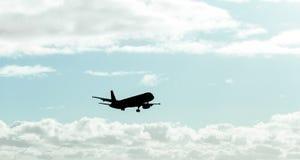 Silhouette, avion dans le ciel Photos stock