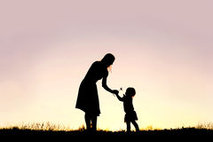 Silhouette of Baby Girl Giving Mom Flower at Sunset. A silhouette of a sweet toddler girl is handing her mother a Daisy flower, in a meadow outside at sunset on stock photo