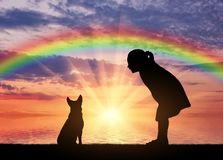 Silhouette of a baby girl and her dog on a background of a sea sunset and a rainbow royalty free stock photography