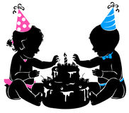 Silhouette baby twins with birthday cake with candle Stock Photos