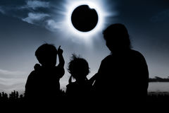 Silhouette back view of family looking at solar eclipse on dark. Natural phenomenon. Silhouette back view of mother and child sitting and relaxing together. Boy royalty free stock photography
