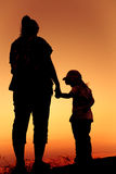 Silhouette back view of mother and daughter clasping hand togeth Stock Photo