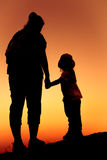 Silhouette back view of mother and daughter clasping hand togeth Stock Image