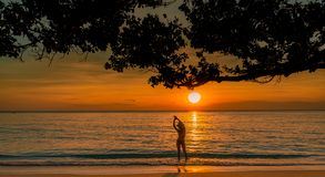 Silhouette back view of woman watching beautiful sunset at tropical paradise beach. Happy girl wear bikini and straw hat stock photo