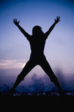 Silhouette back view of woman enjoying and jumping at riverside. Stock Images