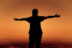 Silhouette back view of woman open arms under the sunrise. Royalty Free Stock Photo