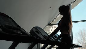 Silhouette back of a Woman is getting ready for a run on a treadmill, morning training healthy fit skinny girl. Silhouette back of a Woman is getting ready for a stock footage