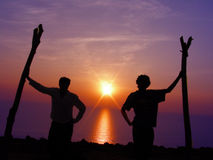 Silhouette Background. Silhouette of two young guys posing in a similar fashion during a sunset, with the suns reflection in water Royalty Free Stock Images