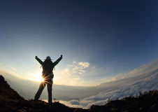 Silhouette of backpacker open arms on sunset mountain Stock Photography