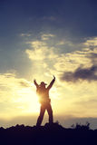 Silhouette of backpacker open arms on sunset mountain Stock Photo