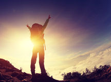 Silhouette of backpacker open arms on sunset mountain Royalty Free Stock Photos