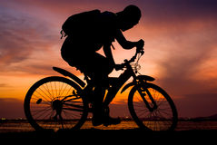 Silhouette of backpacker ride mountain bike Stock Photo
