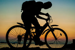 Silhouette of backpacker ride mountain bike beside sea Stock Photography