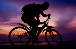 Silhouette of backpacker ride mountain bike beside sea. Silhouette of backpacker ride mountain bike on bridge beside sea with sunset sky background stock photography