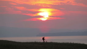 Silhouette of backpacker on sunrise background. stock footage