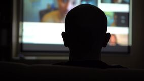 Silhouette of a Bald Head on the Background of the TV. The Concept of a Pleasant Pastime at the Moment of Self-isolation