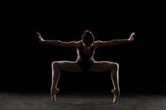 Silhouette ballet dancer in black swimsuit Stock Images