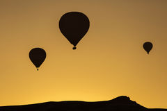 Silhouette of balloons over sunrise in Cappadocia, Turkye Royalty Free Stock Images
