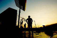 Silhouette of band on stage. Silhouette of band preparing on a stage with sunset stock photo