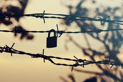 Silhouette of barbed wire with padlock. stock photos