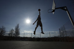 Silhouette basketball player in mid air about to slam dunk Stock Photos